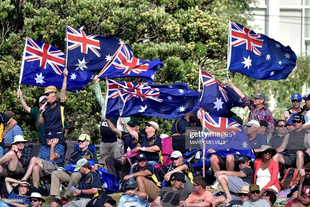 Australian fans wave flags during the first cricket Test match between New Zealand and Australia at the Basin Reserve in Wellington on February 12, 2016. AFP PHOTO / MARTY MELVILLE / AFP / Marty Melville