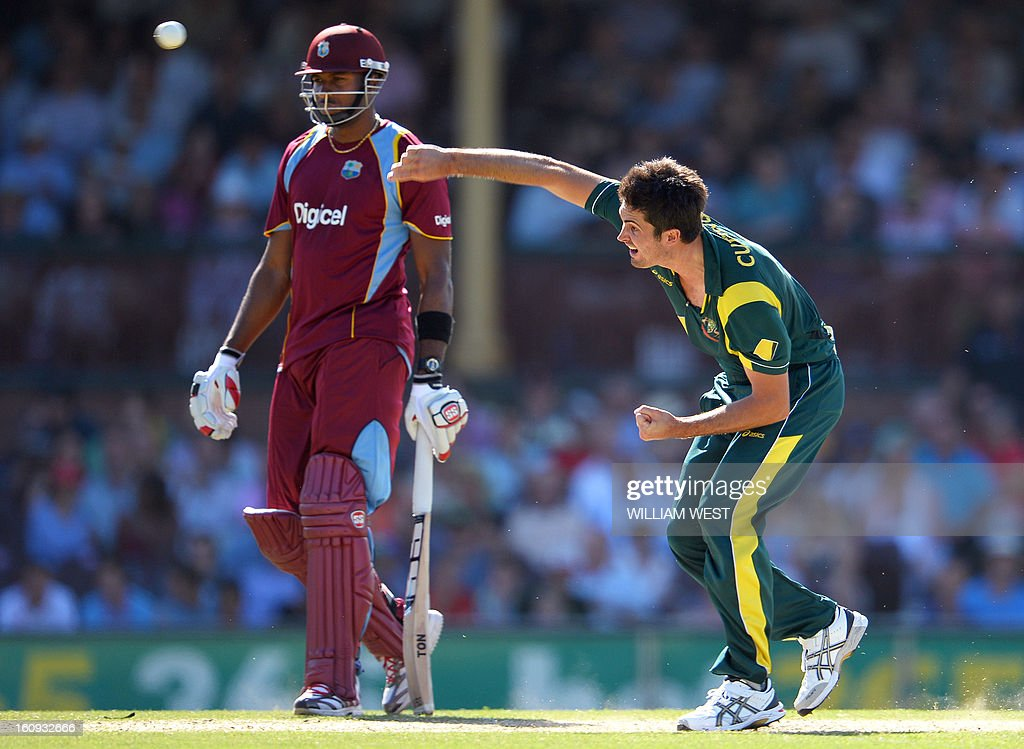 Australian fast bowler Ben Cutting sends down a delivery as West Indies batsman Kieron Pollard (L) looks on in their one-day cricket international played at the Sydney Cricket Ground on February 8, 2013. AFP PHOTO/William WEST IMAGE
