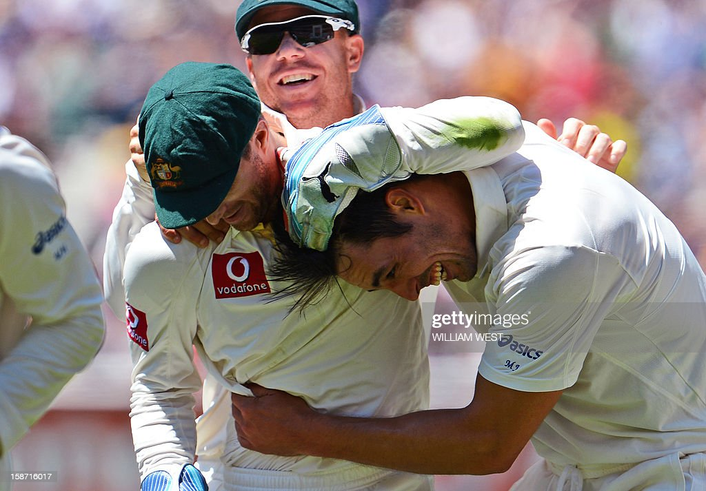 Australian fast bowler Mitchell Johnson (R) celebrates with teammates Matthew Wade (L) and David Warne (C) after they combined to dismiss Sri Lankan batsman Dhammika Prasad with teammates on the first day of the second cricket Test match between Australia and Sri Lanka at the Melbourne Cricket Ground (MCG), in Melbourne, on December 26, 2012. AFP PHOTO/William WEST IMAGE