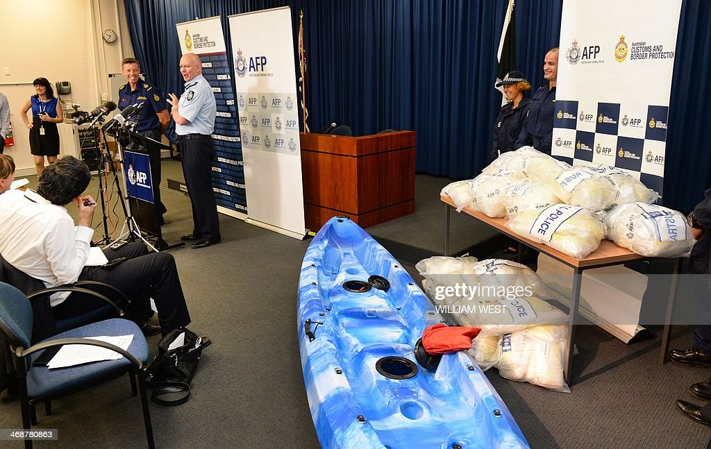Australian Federal Police and Customs officers (L) speak at a press conference after Australian authorities found Aus$180 million (US$162 million) of methamphetamine (R) stashed in a consignment of kayaks from China, in Sydney on February 12, 2014. Four Taiwanese nationals were arrested afte the 183-kilogramme (402-pound) haul was discovered during a joint Australian Federal Police and Customs and Border Protection Service operation at Sydney's container port. AFP PHOTO / William WEST