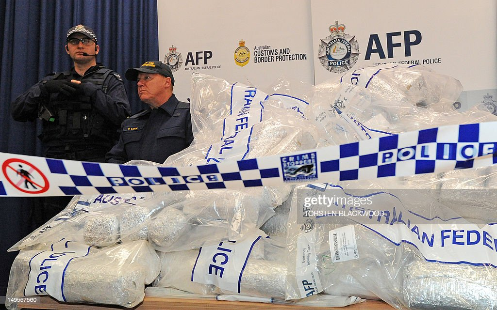 Australian Federal Police (AFP) guard 525 million USD worth of crystal methamphetamine ('ice') and heroin after smashing a Hong Kong-based international drugs syndicate in Sydney on July 31, 2012. It was the largest haul of ice (306 kilograms) in Australian history and the third-biggest heroin bust (252 kilograms) and was the culmination of an 11-month operation following a tip-off from the US Drug Enforcement Administration. AFP PHOTO / Torsten BLACKWOOD