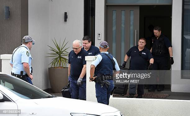 Australian Federal Police officers exit a house as four people were arrested over the terrorlinked murder of a police employee after coordinated...