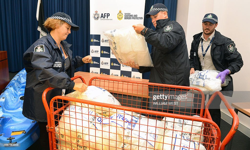 Australian Federal Police officers load methamphetamine to take to a vault after Australian authorities found Aus$180 million (US$162 million) of the drug stashed in a consignment of kayaks from China, in Sydney on February 12, 2014. Four Taiwanese nationals were arrested afte the 183-kilogramme (402-pound) haul was discovered during a joint Australian Federal Police and Customs and Border Protection Service operation at Sydney's container port. AFP PHOTO / William WEST