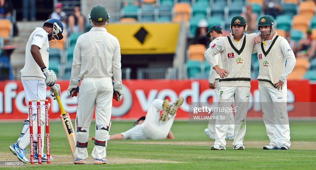 Australian fieldsmen David Warner (2/R) and Phil Hughes (R) talks to Sri Lankan batsman Prasanna Jayawardene (L) on the final day of the first cricket Test match in Hobart on December 18, 2012. AFP PHOTO/William WEST IMAGE