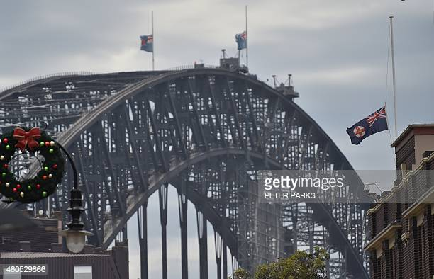 Australian flags fly at half mast on Sydney Harbour bridge following the fatal siege in the heart of Sydney's financial district on December 16 2014...