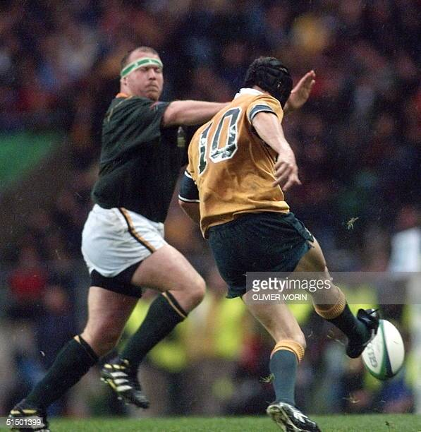 Australian flyhalf Stephen Larkham takes the kick for his drop goal drops the ball as South African prop Cobus Visagie arrives during the Rugby World...