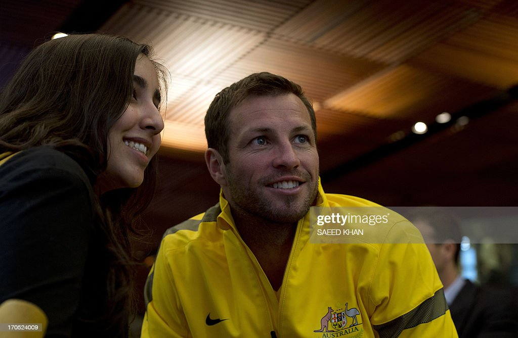 Australian football player Lucas Neill poses for a picture with a fan during a Socceroos public appearance in Sydney on June 14, 2013. Australia will face Iraq in Sydney on June 18 with victory booking them a spot in the 2014 World Cup. AFP PHOTO / Saeed KHAN