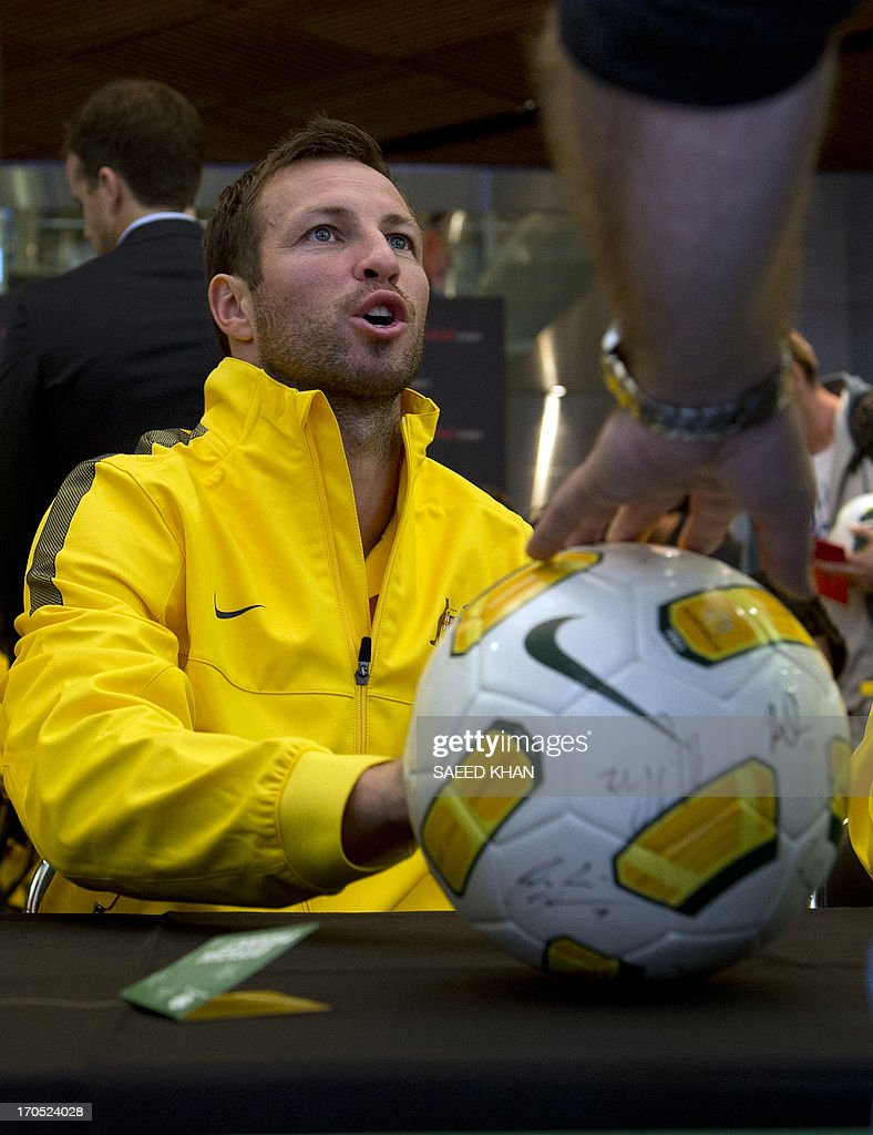 Australian football player Lucas Neill signs an autograph for a fan during a Socceroos public appearance in Sydney on June 14, 2013. Australia will face Iraq in Sydney on June 18 with victory booking them a spot in the 2014 World Cup. AFP PHOTO / Saeed KHAN