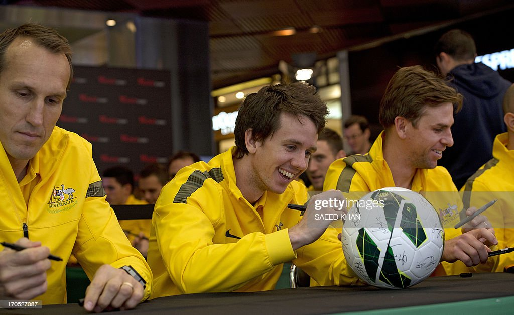 Australian football player Robbie Kruse (C) autographs a football for fans along with teammate Mark Schwarzer (L) during a Socceroos public appearance in Sydney on June 14, 2013. Australia will face Iraq in Sydney on June 18 with victory booking them a spot in the 2014 World Cup. AFP PHOTO / Saeed KHAN