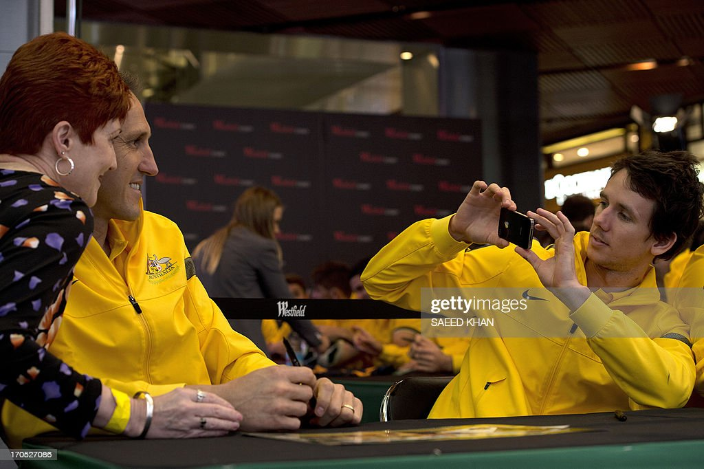 Australian football player Robbie Kruse (R) takes a picture of teammate Mark Schwarzer (2nd L) with a fan during a Socceroos public appearance in Sydney on June 14, 2013. Australia will face Iraq in Sydney on June 18 with victory booking them a spot in the 2014 World Cup. AFP PHOTO / Saeed KHAN