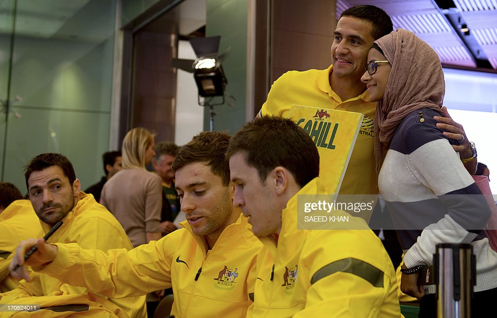Australian football player Tim Cahill (top C) poses for a photograph with a fan during a Socceroos public appearance in Sydney on June 14, 2013. Australia will face Iraq in Sydney on June 18 with victory booking them a spot in the 2014 World Cup. AFP PHOTO / Saeed KHAN