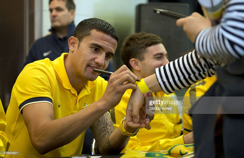 Australian football player Tim Cahill (L) signs an autograph for a fan during a Socceroos public appearance in Sydney on June 14, 2013. Australia will face Iraq in Sydney on June 18 with victory booking them a spot in the 2014 World Cup. AFP PHOTO / Saeed KHAN