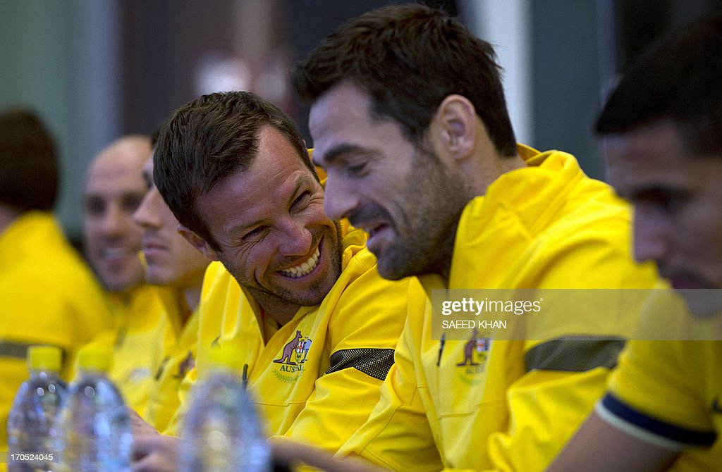 Australian football players Lucas Neill (L) and Sasa Ognenovski (2nd R) share a light moment during a Socceroos public appearance in Sydney on June 14, 2013. Australia will face Iraq in Sydney on June 18 with victory booking them a spot in the 2014 World Cup. AFP PHOTO / Saeed KHAN