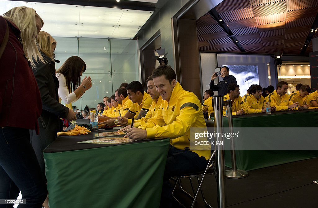 Australian football players sign autographs for fans during a Socceroos public appearance in Sydney on June 14, 2013. Australia will face Iraq in Sydney on June 18 with victory booking them a spot in the 2014 World Cup. AFP PHOTO / Saeed KHAN