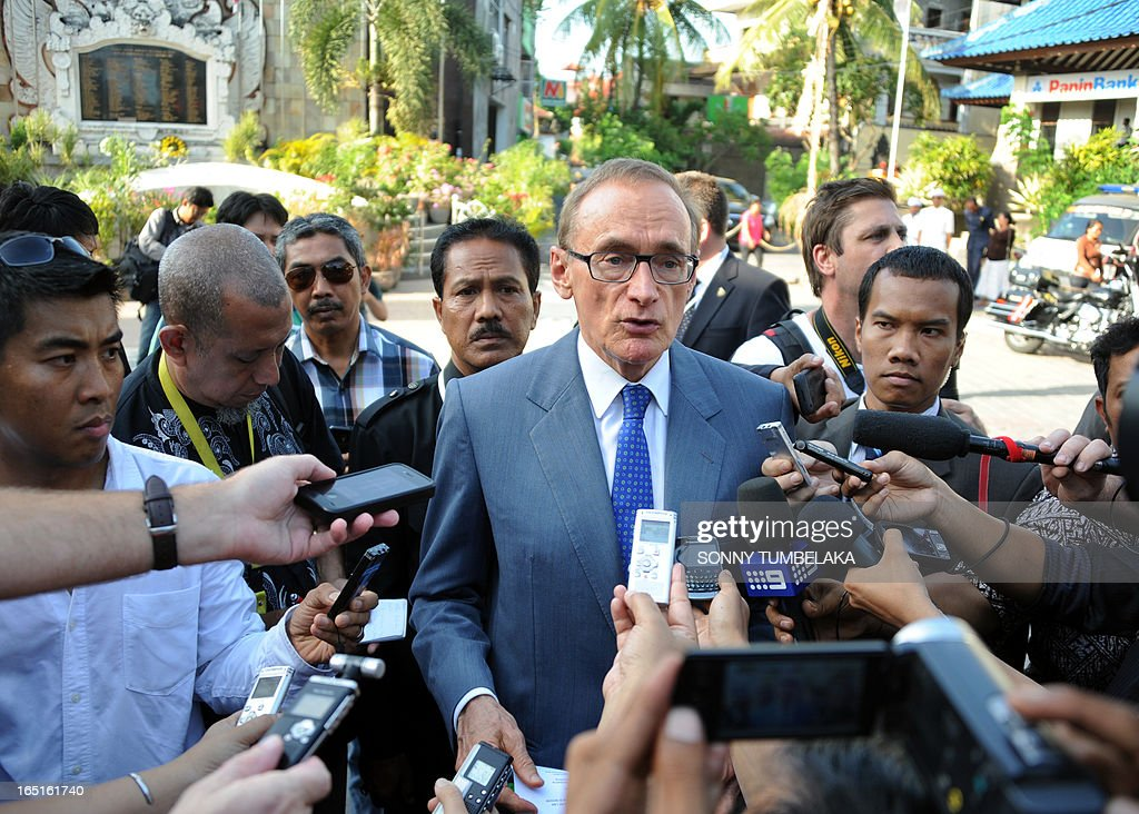 Australian foreign minister Bob Carr (C) speaks to journalists after laying a wreath at a monument for victims of 2002 Bali in Kuta on Bali island on April 1, 2013. Carr is on the resort island of Bali to attend the fifth Bali Regional Ministerial Conference on people smuggling, trafficking in Persons and telated transnational crime.