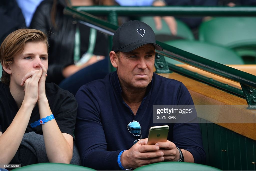 Australian former cricketer Shane Warne watches on Centre Court as Britain's Andy Murray plays against Britain's Liam Broady during their men's singles first round match on the second day of the 2016 Wimbledon Championships at The All England Lawn Tennis Club in Wimbledon, southwest London, on June 28, 2016. / AFP / GLYN