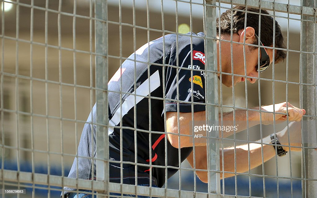 Australian Formula One driver Mark Webber climbs a fence at Interlagos motorsport circuit in Sao Paulo on November 22, 2012 ahead of the Brazilian Grand Prix this weekend.