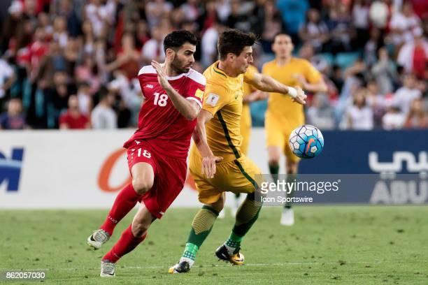 Australian forward Tomi Juric gets the ball around Syrian midfielder Zaher Medani at the Soccer World Cup Qualifier between Australia and Syria on...