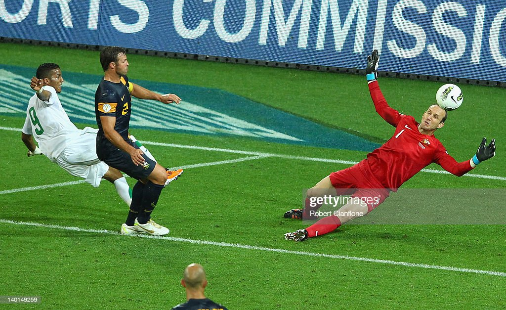 Australian goalkeeper <a gi-track='captionPersonalityLinkClicked' href=/galleries/search?phrase=Mark+Schwarzer&family=editorial&specificpeople=208085 ng-click='$event.stopPropagation()'>Mark Schwarzer</a> makes a save off Naif Ahmed Hazazi of Saudi Arabia during the Group D 2014 FIFA World Cup Asian Qualifier match between Australia and Saudi Arabia at AAMI Park on February 29, 2012 in Melbourne, Australia.
