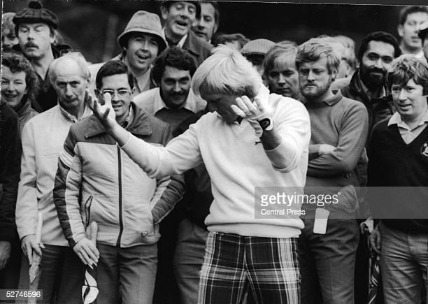 Australian golfer Greg Norman holds out his hands and bows his head after a problem at the 13th hole during the Suntory World Matchplay Championship...