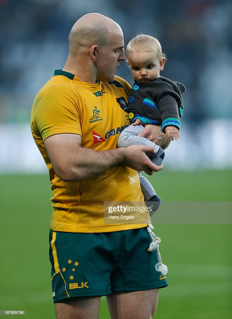 Australian hooker Stephen Moore holds his son on the pitch after his side won the international match between Italy and Australia at the Stadio Olimpico on November 9, 2013 in Turin, Italy.