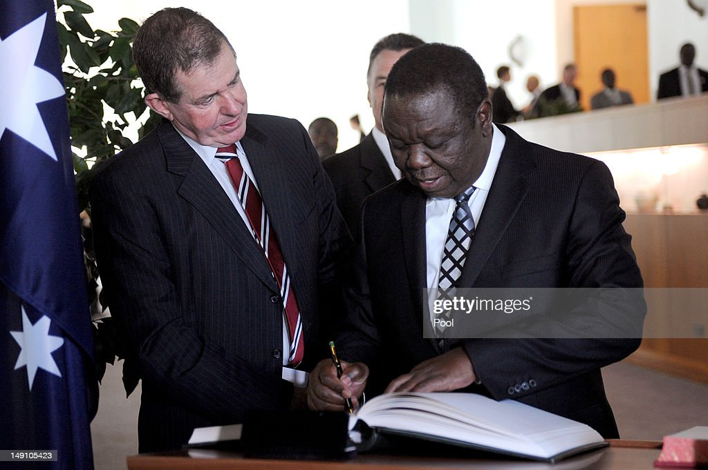 Australian House of Representatives Speaker Peter Slipper watches as the Prime Minister of Zimbabwe <a gi-track='captionPersonalityLinkClicked' href=/galleries/search?phrase=Morgan+Tsvangirai&family=editorial&specificpeople=800701 ng-click='$event.stopPropagation()'>Morgan Tsvangirai</a> signs the Parliament House visitors book during a lunch on July 23, 2012 in Canberra, Australia. Australia is the third largest donor to Zimbabwe with assistance focused on water, sanitation and economic growth.