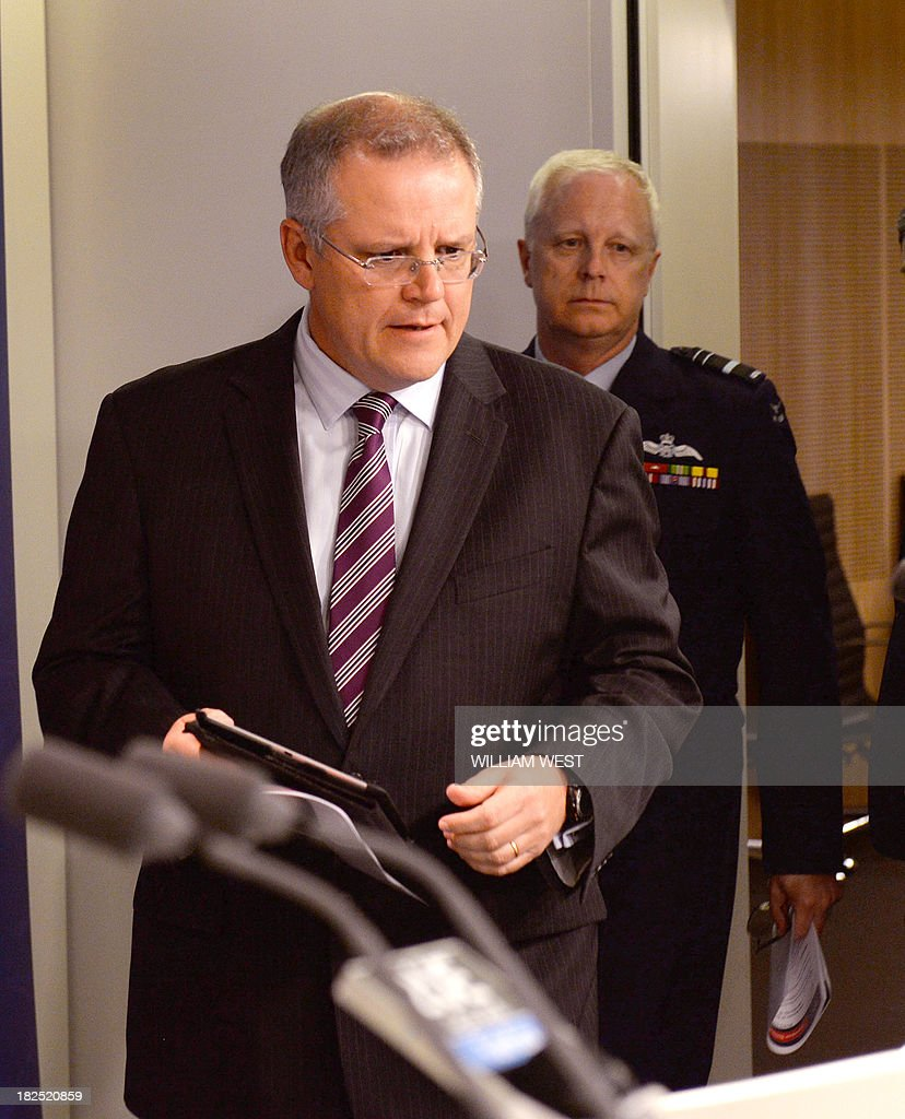 Australian Immigration Minister Scott Morrison (L) and Air Marshal Mark Binskin (R) arrive for a press conference in Sydney on September 30, 2013, where Morrison rejected claims that Australian authorities took too long to respond to distress calls from an asylum seeker boat which went down off the coast of Java, killing at least 31 people. Morrison held the second of his weekly briefings on asylum seeker matters as Australian Prime Minister Tony Abbott heads to Jakarta for his first international meeting as Prime Minister, where the boat people issue will high on the agenda of bilateral discussions with his Indonesian counterpart, president Susilo Bambang Yudhoyono. AFP PHOTO/William WEST