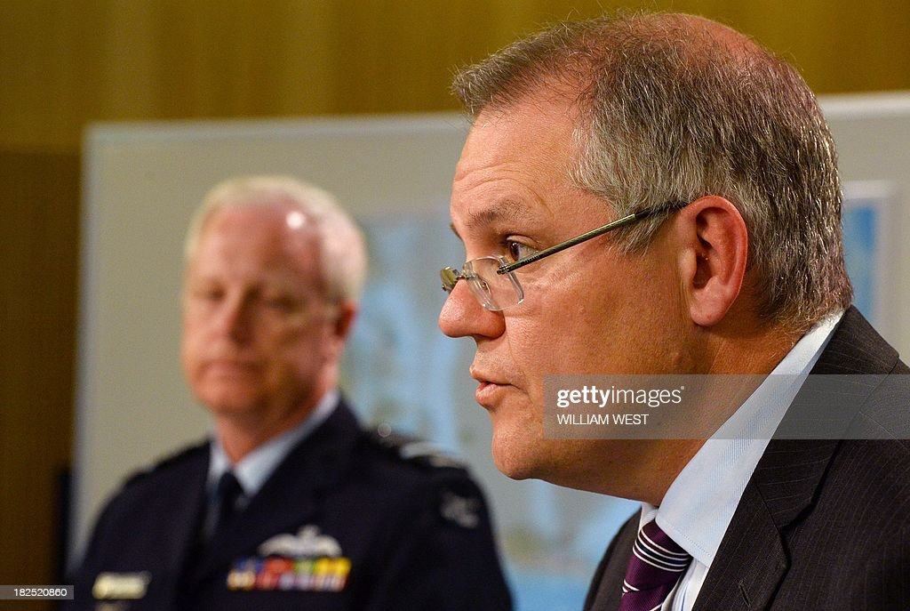Australian Immigration Minister Scott Morrison (R) speaks as Air Marshal Mark Binskin (L) listens during a press conference in Sydney on September 30, 2013, where Morrison rejected claims that Australian authorities took too long to respond to distress calls from an asylum seeker boat which went down off the coast of Java, killing at least 31 people. Morrison held the second of his weekly briefings on asylum seeker matters as Australian Prime Minister Tony Abbott heads to Jakarta for his first international meeting as Prime Minister, where the boat people issue will high on the agenda of bilateral discussions with his Indonesian counterpart, president Susilo Bambang Yudhoyono. AFP PHOTO/William WEST