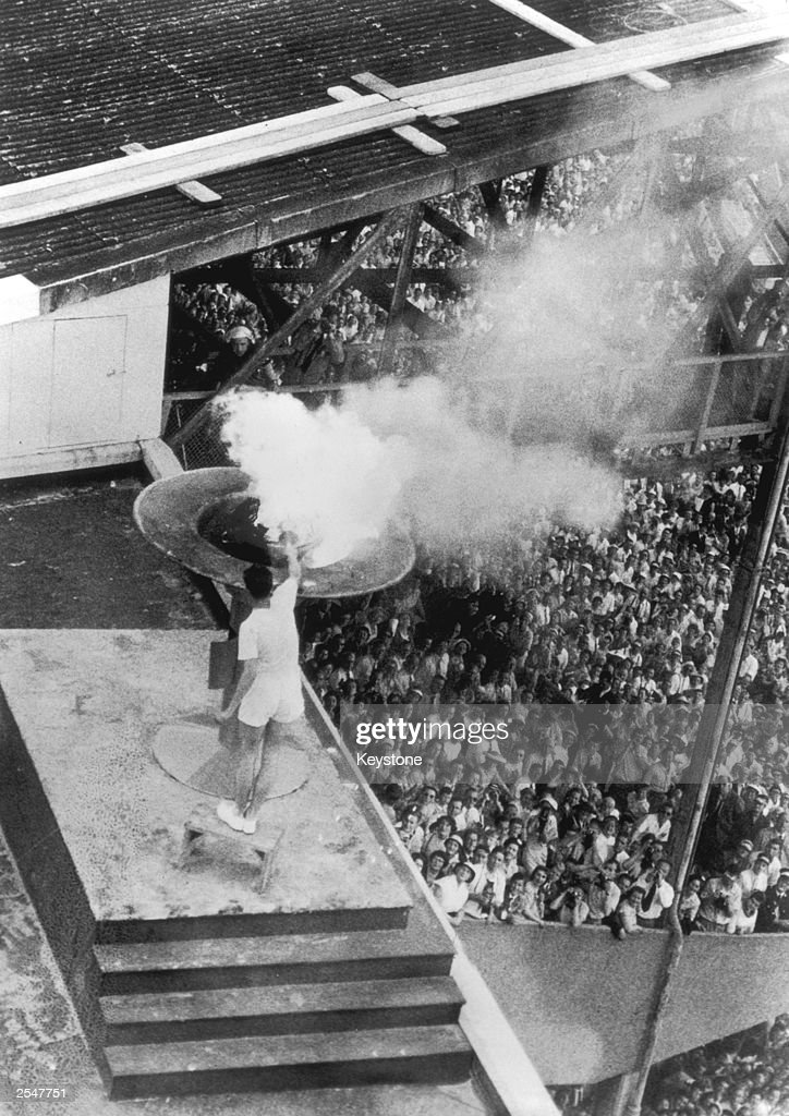Australian junior mile champion Ron Clarke lights the Olympic flame with a torch at the opening ceremony for the Olympic Games in Melbourne, 26th November 1956.