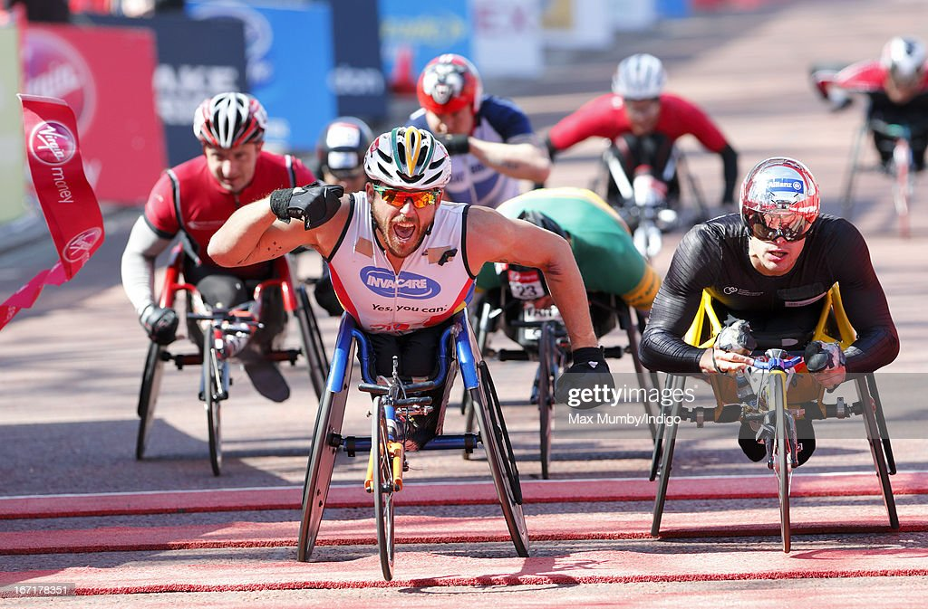 Australian Kurt Fearnley punches the air as crosses the finish line to win the men's wheelchair race at the Virgin London Marathon 2013 on April 21, 2013 in London, England.