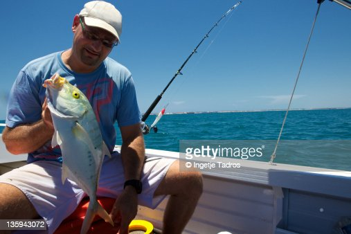 Australian man catching a big fish stock photo getty images for Catching big fish