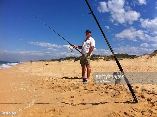 Australian man fishing in the Tasman Sea on Ninety Mile Beach Lakes Entrance Victoria Australia