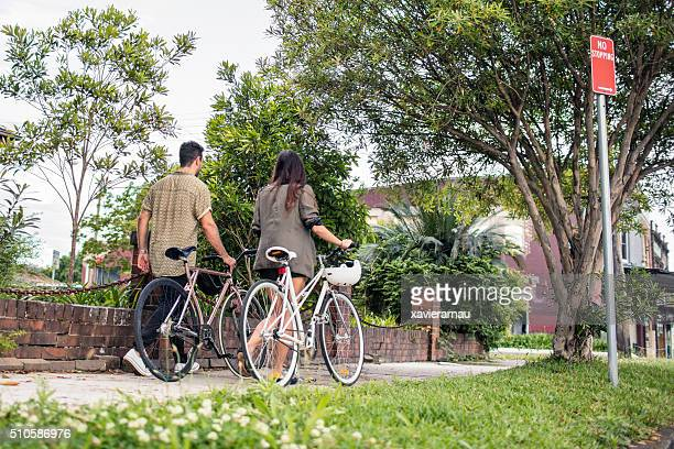 Australian mid adult couple walking with their bikes back home