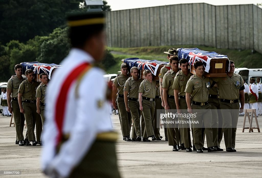 Australian Military personell carry coffins with the remains of their soldiers and dependents during a repatriation ceremony at the Royal Malaysian Airforce base in Subang on May 31, 2016. Decades after the end of the Vietnam war and the brutal fight against communists insurgency in Malaysia, the remains of 24 Australians soldiers and eight dependents were returned home. / AFP / MANAN