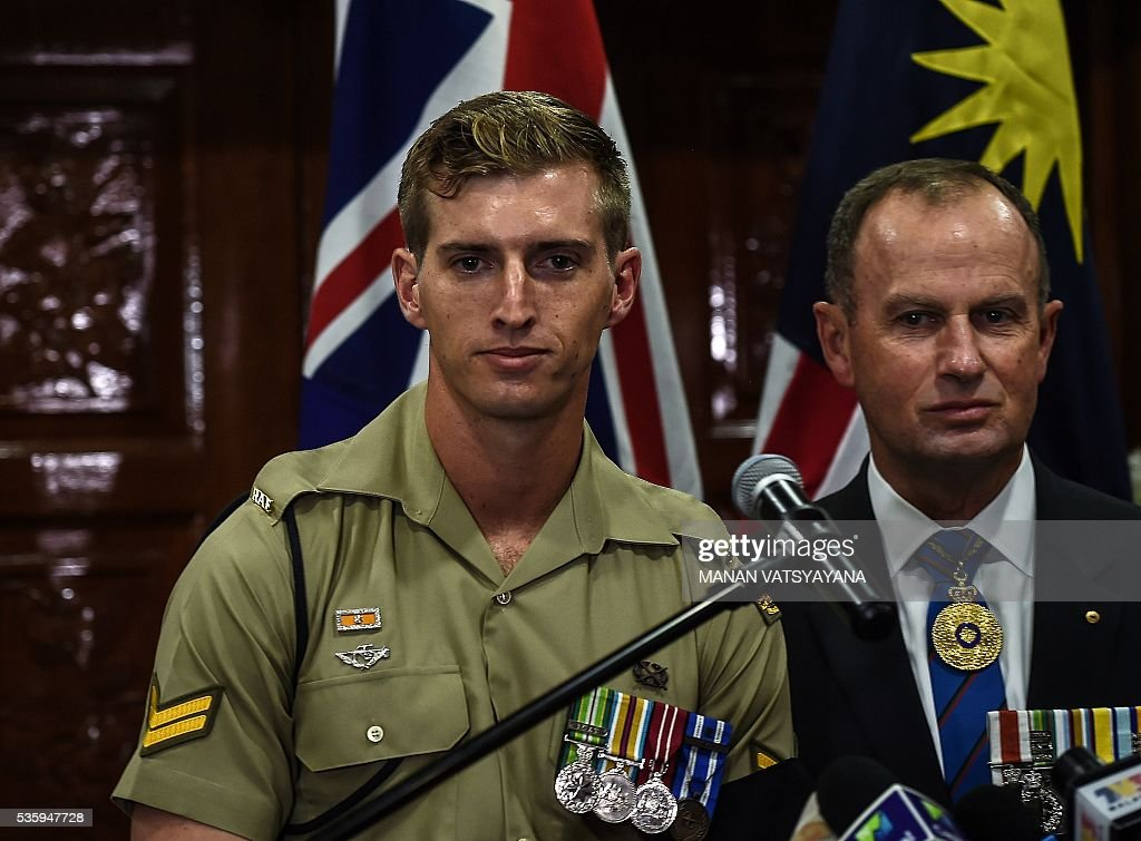 Australian military personell Christopher Bowtell (L), whose late grandfather Robert Walter Bowtell's remains were sent back, attends a repatriation ceremony at the Royal Malaysian Airforce base in Subang on May 31, 2016. Decades after the end of the Vietnam war and the brutal fight against communists insurgency in Malaysia, the remains of 24 Australians soldiers and eight dependents were returned home. / AFP / MANAN