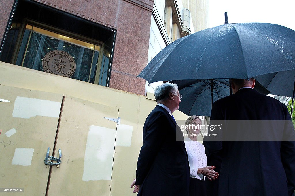 Australian Minister for Foreign Affairs, Julie Bishop speaks with NSW Premier Mike Baird and UK Secretary of State for Defence, Michael Fallon at the site of the Lindt Cafe Siege at Martin Place on February 2, 2015 in Sydney, Australia. On December 15 2014, gunman Man Haron Monis was shot dead by police after taking hostages at the Lindt Chocolat Cafe in Martin Place. Two other people died, 33-year-old cafe manager Tori Johnson and 38-year-old Sydney barrister Katrina Dawson.