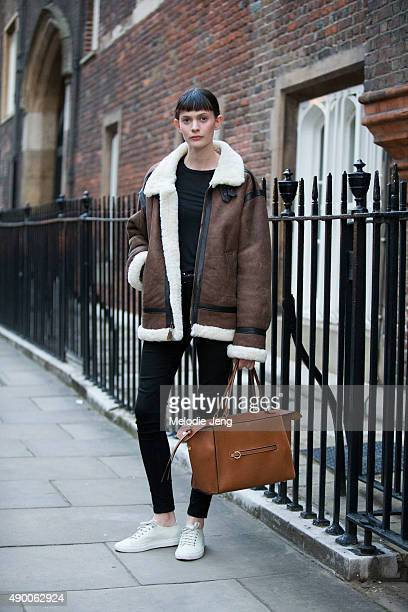 Australian model Chloe Wheatcroft wears a brown shearling coat black skinny jeans and a brown Celine tote bag during London Fashion Week Spring...