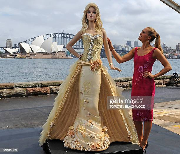 Australian model Erika Heynatz touches a 21 metre high 'Barbie doll' chocolate mud cake to celebrate the 50th anniversary of the world's most popular...