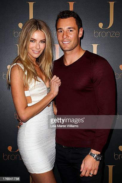Australian model Jennifer Hawkins poses with partner Jake Wall at the launch of her new selftanning range 'J Bronze' at Bondi Beach on August 15 2013...
