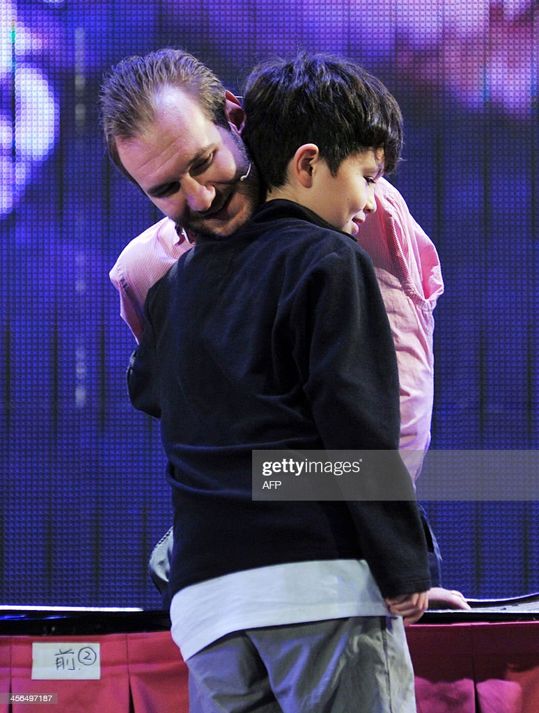 Australian motivational speaker Nick Vujicic hugs a boy during during an event where he also delivered a speech to 50,000 spectators at the Taipei World Trade Center Nangang Exhibition Hall on December 14, 2013. Vujicic is on a three-day visit to Taiwan financed by a local private business and the Red Heart Association to deliver two speeches for a total of 100,000 people from December 14. AFP PHOTO / Mandy CHENG