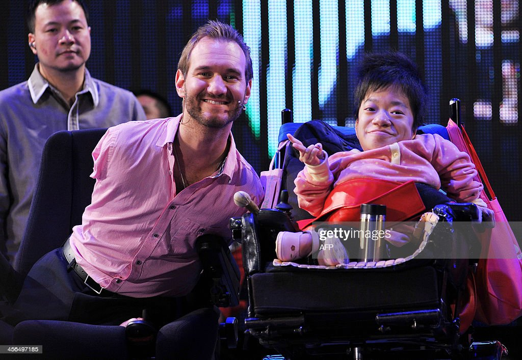 Australian motivational speaker Nick Vujicic (L) poses for photos with a disabled participant during an event where he also delivered a speech to 50,000 spectators at the Taipei World Trade Center Nangang Exhibition Hall on December 14, 2013. Vujicic is on a three-day visit to Taiwan financed by a local private business and the Red Heart Association to deliver two speeches for a total of 100,000 people from December 14. AFP PHOTO / Mandy CHENG