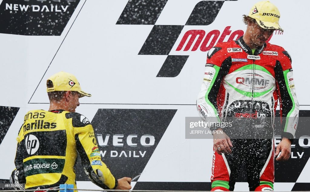Australian Moto2 rider Anthony West (R) celebrates winning on the podium with third-placed Finnish rider Mika Kallio (L) during the Motorcycling Grand Prix of Assen held at TT circuit in Assen, northern Netherlands, on June 28, 2014.