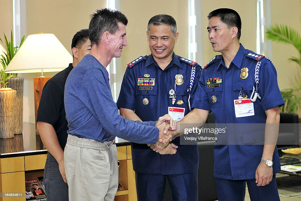 Australian national Warren Rodwell is greeted by Philippine National Police officials before he delivers a short statement to the media at Manila International Airport on March 25, 2013 in Manila, Philippines. Rodwell was reportedly released on March 23 after allegedly paying $90,000 USD to secure his safety after being held as a hostage of Islamic militants in the southern Philippines for 15 months.