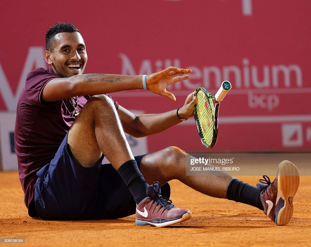 Australian Nick Kyrgios laughs after falling on the pitch playing against Croatian Borna Coric during their quarter-final Estoril Open Tennis tournament in Estoril on April 29, 2016. / AFP / JOSE