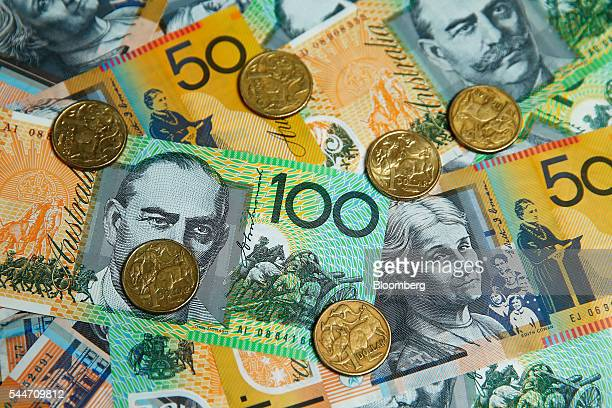 Australian onedollar coins onehundred dollar and fifty dollar banknotes are arranged for a photograph in Sydney Australia on Monday July 4 2016...