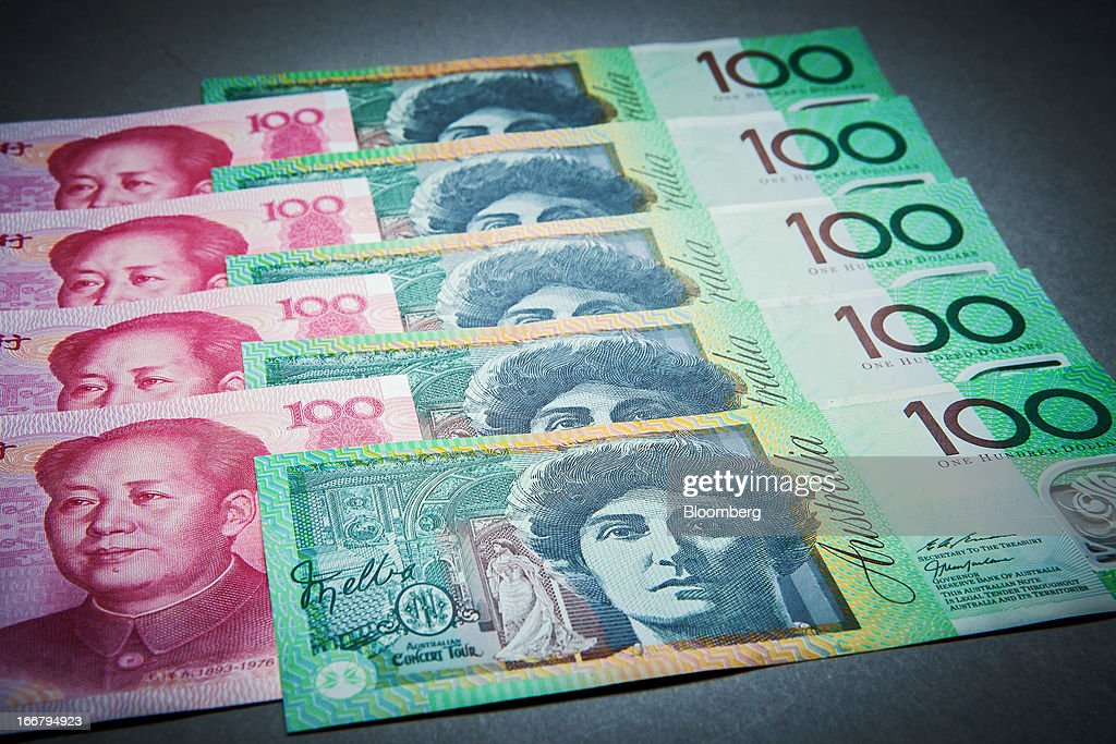 Australian one-hundred dollar banknotes, right, and Chinese one-hundred yuan banknotes are arranged for a photograph in Sydney, Australia, on Wednesday, April 17, 2013. Direct trading between the Australian dollar and yuan started on April 10. Photographer: Ian Waldie/Bloomberg via Getty Images