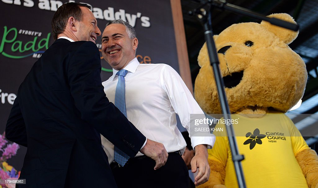 Australian opposition leader Tony Abbott (L) and Shadow Treasurer Joe Hockey come on the stage during a first season mango auction at the Flemington Sydney market on September 4, 2013. Australian election frontrunner Tony Abbott vowed Asia will be his main foreign policy focus if he assumes office, as an influential media group turned on incumbent Prime Minister Kevin Rudd. AFP PHOTO / Saeed KHAN