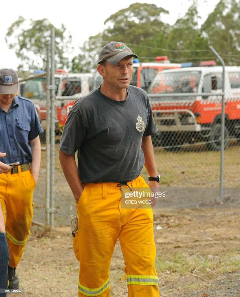 Australian Opposition Leader Tony Abbott (C) arrives to help in his capacity as a member of the rural fire service at the incident control centre at Nowra on the south coast of Australia's New South Wales state on January 9, 2013. Cooler conditions helped firefighters battling blazes across Australia on January 9 but up to 30 were still out of control, destroying a handful of homes and killing thousands of livestock. AFP PHOTO / Greg WOOD