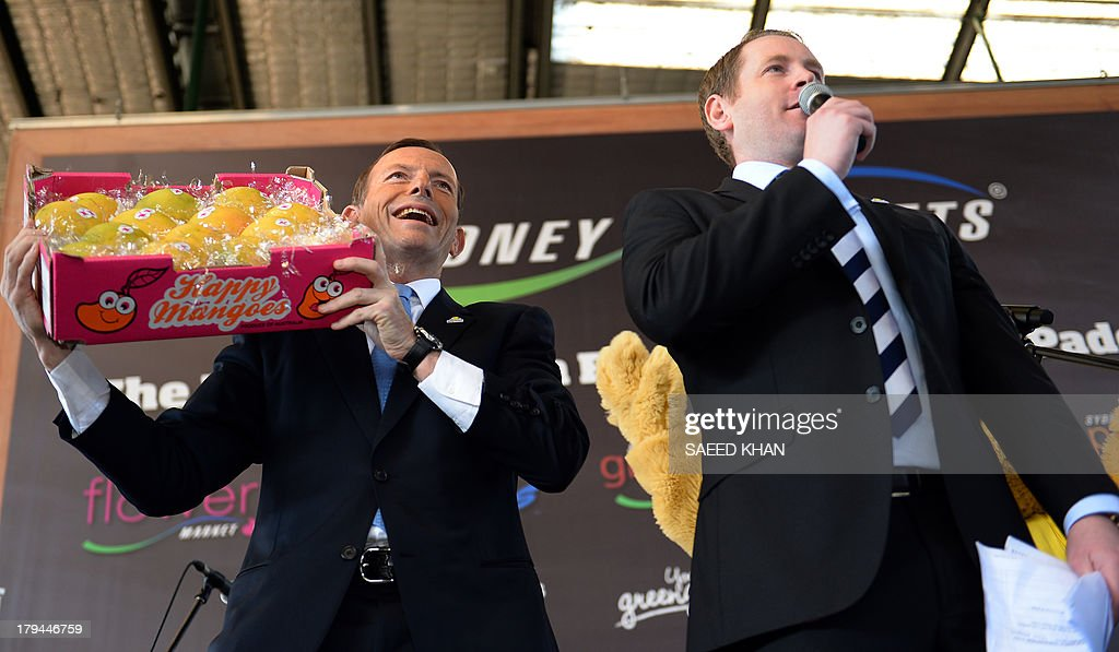 Australian opposition leader Tony Abbott (L) carries a crate of mangoes during an annual auction at the Sydney market at Flemington on September 4, 2013. The auction was organised by the Sydney markets foundation and proceeds from the first box of mangoes auctioned will be distributed to OzHarvest, the prostate cancer foundation of Australia and cancer council of New South Wales. AFP PHOTO / Saeed KHAN