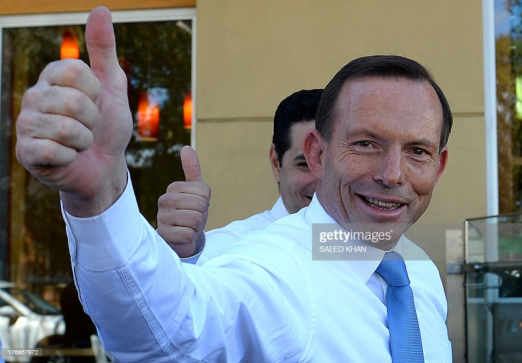 Australian opposition leader Tony Abbott gestures to shoppers during a street walk in the Liverpool suburbs of Sydney on August 19, 2013. A defiant Australian Prime Minister Kevin Rudd warned not to write him off as a new poll showed his popularity slumping barely three weeks away from elections. After a fortnight of relentless campaigning, a Newspoll for The Australian newspaper showed voter satisfaction with him at 35 percent, down four points, while conservative rival Tony Abbott saw a three-point jump to 41 percent. AFP PHOTO / Saeed KHAN